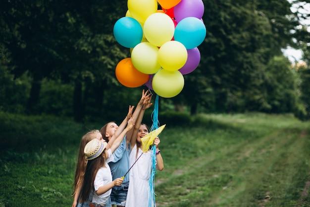 Mała dziewczynka przyjaciele z balonami w lesie