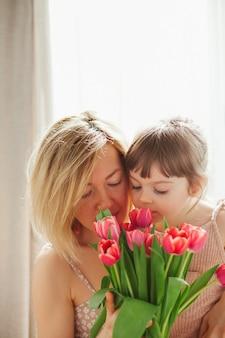 Mała dziewczynka przytula matkę i wącha tulipany. szczęśliwego dnia matki! rodzinne wakacje i razem.