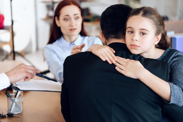 Mała dziewczynka przytula mężczyznę w garniturze siedzi naprzeciwko kobiety.