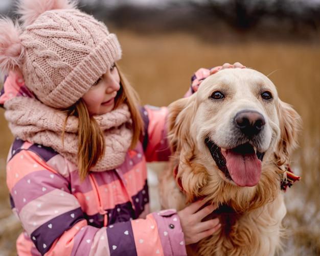 Mała dziewczynka przytula psa rasy golden retriever