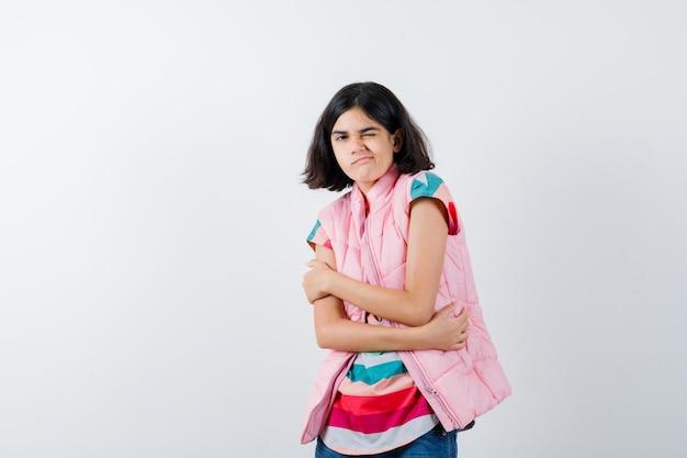 Mała dziewczynka przytula się w t-shirt, kamizelkę puchową, dżinsy i wygląda na zdziwioną, widok z przodu.