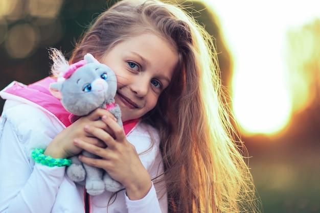 Mała dziewczynka przytulająca ulubionego pluszaka - kota na spacer po parku w słoneczny dzień. na zdjęciu jest puste miejsce na twój tekst