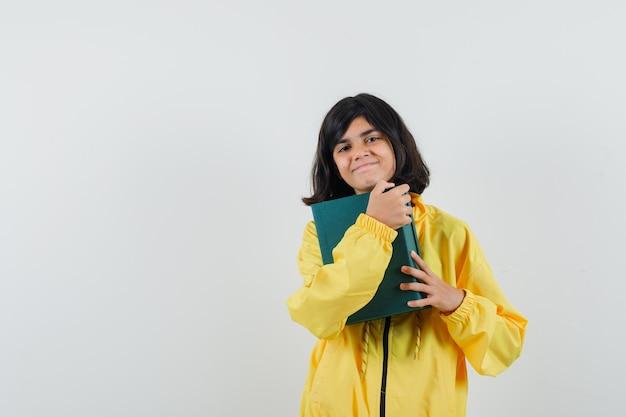 Mała dziewczynka przytulanie obecnego pudełka w żółtej bluzie z kapturem i patrząc wesoło. przedni widok.