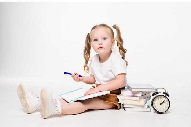 Mała dziewczynka r. na podłodze i rysowanie zdjęć w notesie na białym tle