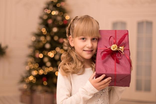 Mała dziewczynka rano znalazła pod choinką prezent od świętego mikołaja.