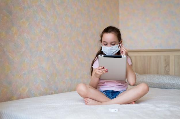 Mała dziewczynka rasy białej w masce ochronnej z tabletem siedzi w domu w trybie samowyizolacji