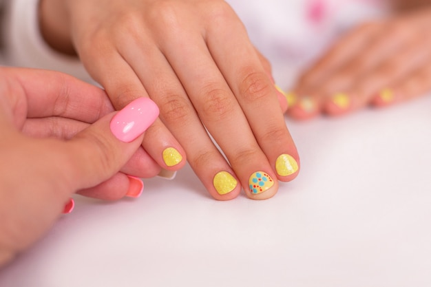 Mała dziewczynka ręce z żółtymi paznokciami do manicure, kwiatki