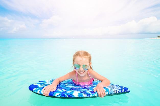 Mała dziewczynka relaksuje na nadmuchiwanej lotniczej materac w morzu