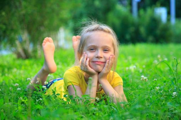 Mała dziewczynka relaksuje na trawie