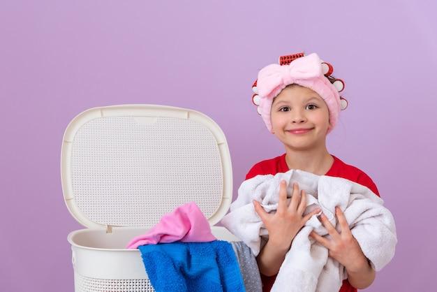 Mała dziewczynka robi domowe pranie z lokówek na głowie na fioletowym tle