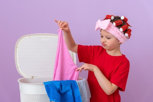 Mała dziewczynka robi domowe pranie z lokówkami na głowie na fioletowym tle