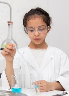 Mała dziewczynka robi eksperyment naukowy w szkole