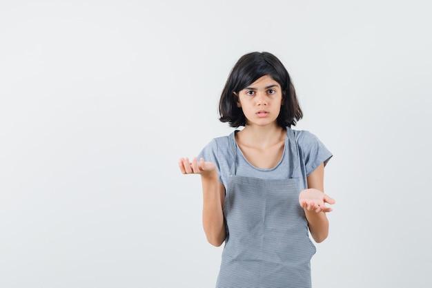 Mała dziewczynka robi gest wagi w t-shirt, fartuch i patrząc zdezorientowany, widok z przodu.