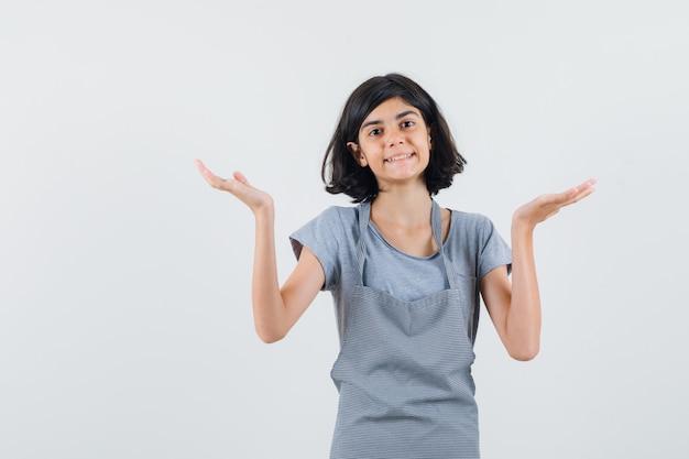 Mała dziewczynka robi gest wagi w t-shirt, fartuch i wesoły, widok z przodu.