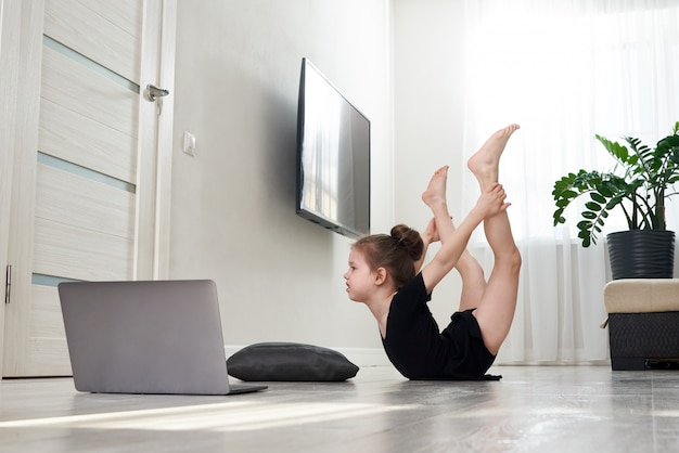Mała dziewczynka robi gimnastykom ćwiczy w domu używać online uczenie z laptopem, internet edukaci pojęcie