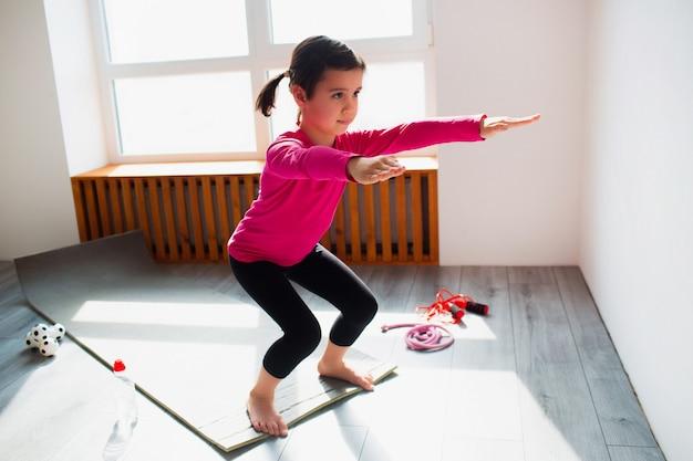 Mała dziewczynka robi kucniętym ćwiczeniom trening w domu. słodkie dziecko trenuje na macie wewnątrz. mała ciemnowłosa modelka w odzieży sportowej ma ćwiczenia w pobliżu okna w swoim pokoju