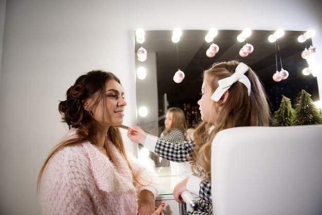Mała dziewczynka robi makijaż dla swojej mamy przed lustrem.