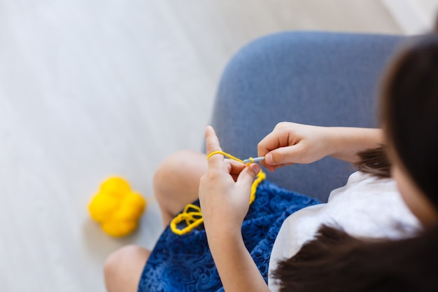 Mała dziewczynka robi na drutach na szydełku. dziewczyna siada na kanapie i robi na drutach z włóczki. grube nici na szydełku. komfort w domu.