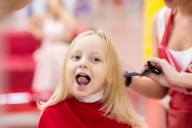 Mała dziewczynka robi ostrzyżeniu przy salonem.