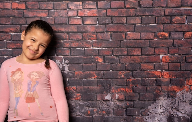 Mała dziewczynka robi pozy przed starym tle ściany z cegły, ciemne tło, selektywny fokus.