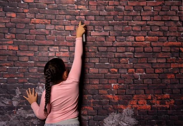 Mała dziewczynka robi pozy z sprayem przed starym tle ściany z cegły, ciemne tło, selektywne focus.