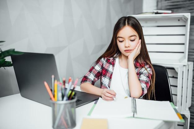 Mała dziewczynka robi pracie domowej przy stołem w żywym pokoju.