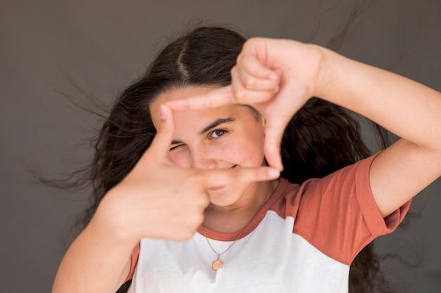 Mała dziewczynka robi ramie z jej palcami