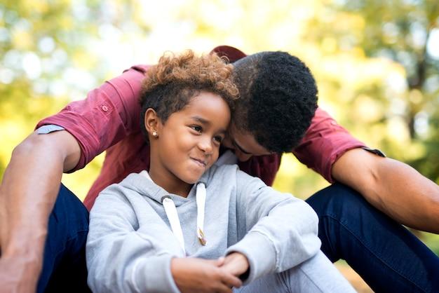 Mała dziewczynka robi słodkie miny, podczas gdy jego ojciec śmieje się głośno
