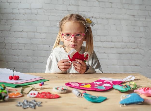 Mała dziewczynka robi świąteczne dekoracje z filcu, świąteczne rzemiosło