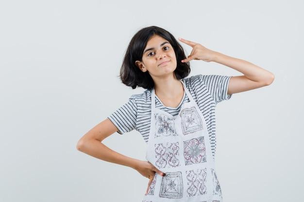 Mała dziewczynka robi symbol rocka w t-shirt, fartuch i wygląda pewnie.