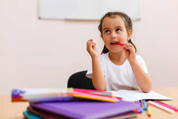 Mała dziewczynka robi szkolnej pracie w domu