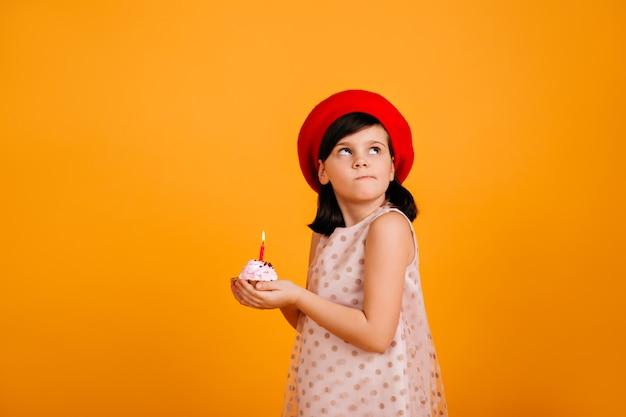 Mała dziewczynka robi życzenia urodzinowe. brunetka dzieciak trzyma tort ze świecą na żółtej ścianie.