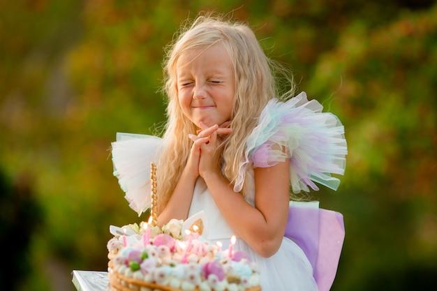 Mała dziewczynka robi życzenie i zdmuchuje świeczki na torcie