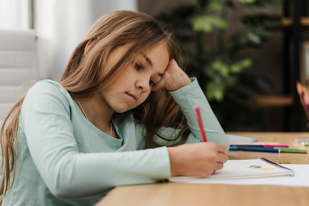 Mała dziewczynka robienie notatek, będąc znudzonym w domu