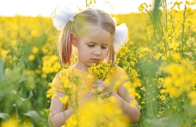Mała dziewczynka romantyczna w polu z żółtymi kwiatami