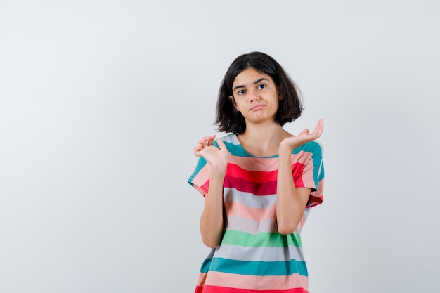 Mała dziewczynka rozciągając ręce w sposób przesłuchania w t-shirt, dżinsy i patrząc zdezorientowany. przedni widok.