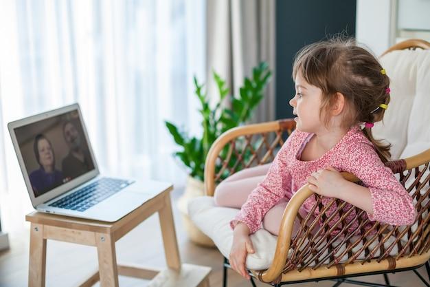 Mała dziewczynka rozmawia na wideo z dziadkami za pomocą laptopa