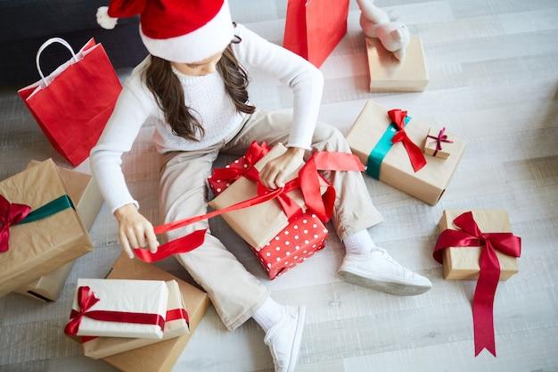 Mała dziewczynka rozpakowywanie prezentów świątecznych, szczęśliwy dzień