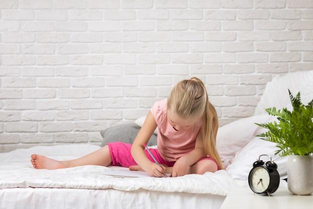 Mała dziewczynka rysowania zdjęć podczas leżenia na łóżku.