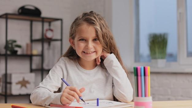 Mała dziewczynka rysowanie obrazków pisakiem na białej księdze albumu siedzi przy stole. zabawa sama, twórcza działalność artystyczna w domu.