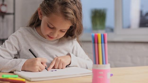 Mała dziewczynka rysowanie obrazków pisakiem na białej księdze albumu. zabawa sama, twórcza działalność artystyczna w domu.
