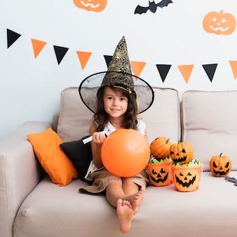 Mała dziewczynka rysuje halloween balonu