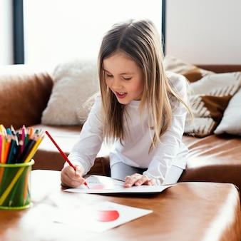 Mała dziewczynka rysuje kartkę z dniem ojca jako niespodziankę dla swojego taty