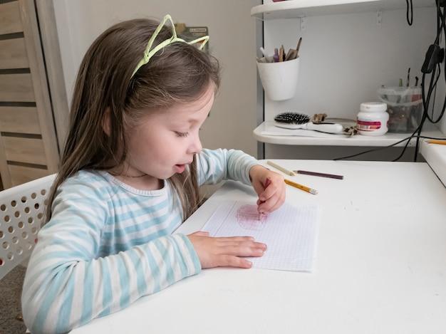Mała dziewczynka rysuje kredkami lewą ręką