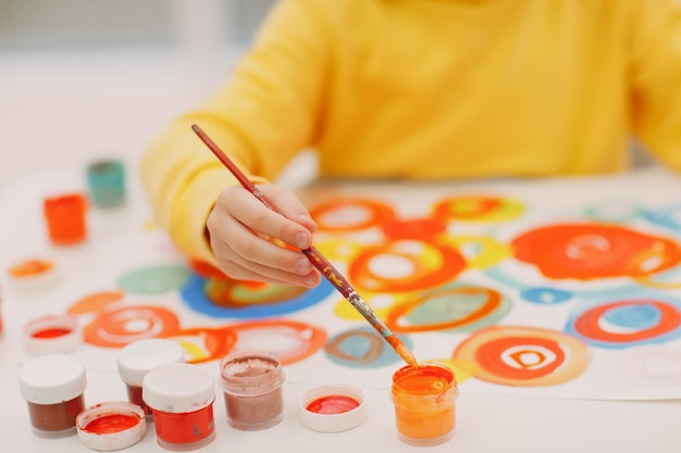 Mała dziewczynka rysuje obraz malarski pędzlem i farbami gwaszowymi z bliska