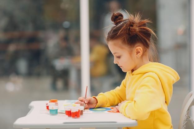 Mała dziewczynka rysuje obraz malowany pędzlem i farbami akwarelowymi