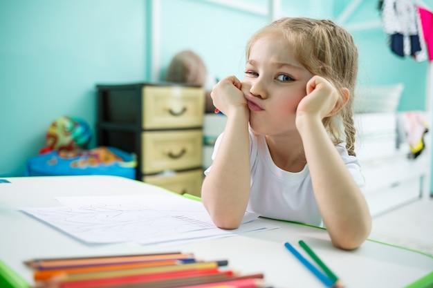 Mała dziewczynka rysuje siedząc przy stole w pokoju na tle ściany