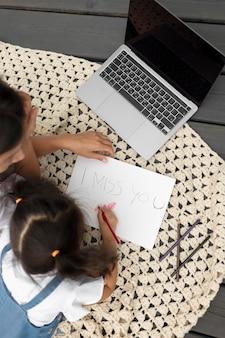 """Mała dziewczynka rysuje wiadomość """"tęsknię za tobą"""" dla swojego taty"""