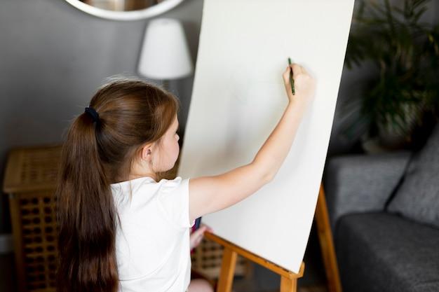 Mała Dziewczynka Rysuje Za Pomocą Sztalugi Darmowe Zdjęcia