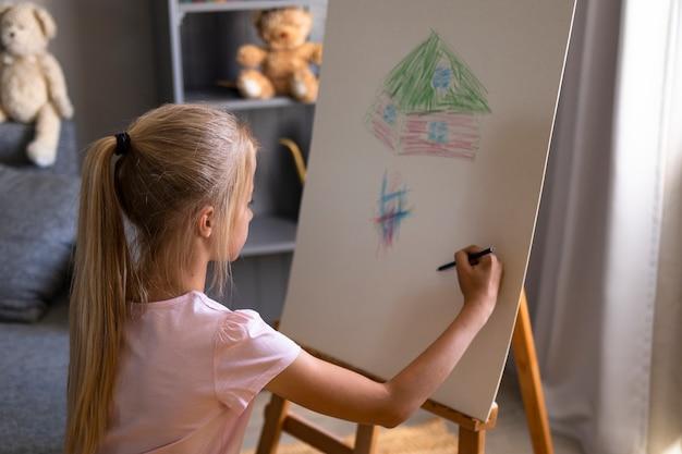 Mała dziewczynka rysuje za pomocą sztalugi